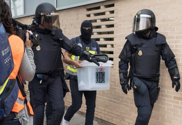 Les forces anti-émeutes de la Guardia Civil ont saisi une des 10.000 urnes fabriquées en Chine. Arrivées en contrebande, cachées dans les greniers et les caves, les églises, les mairies ou des locaux d'entreprises, elles apparaissent triomphalement au grand jour à l'aube du 1er octobre.
