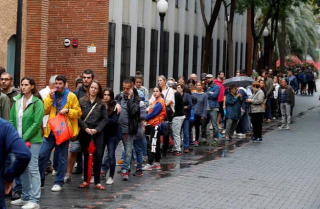 Longues colonnes d'attentes devant les bureaux de vote. Les entraves de la Guardia Civil pour se connecter avec les listes électorales disponibles sur le net retardent les opérations de vote.  Jusqu'à cinq heures d'attente, comme à Vic. Face aux agressions de la Guardia Civil, le président et les membres du gouvernement lancent des appels au calme et à la sérénité : seule la «force tranquille» de tout un peuple doit répondre à la violence des forces de «l'ordre».