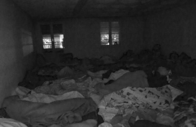 Enroulés dans des couvertures à même le sol, les voyageurs roupillent d'épuisement.