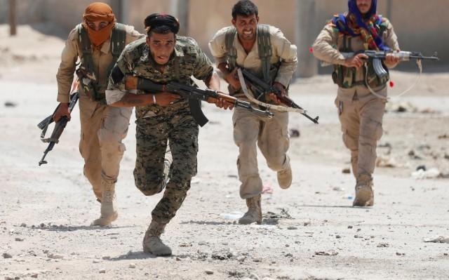 Des combattants kurdes montent à l'assaut dans la ville de Raqqa en 2017, contre l'Etat islamique