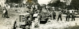 26 juillet 1965. Suite à leur succès au « possessoire » les agriculteurs vont essayer de reprendre effectivement possession de leurs terrains mais ils devront rebrousser chemin sous la menace du bulldozer de l'entreprise DAVID. On est passé là tout près d'un incident grave. On aperçoit au fond les partisans du maire CAMI qui vont conspuer les agriculteurs dans les minutes qui suivront cet instantané. Photo ADPALAA.